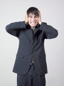 image of stressed businessman covering his ears