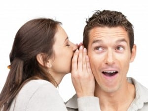 woman whispering on to a mans ear